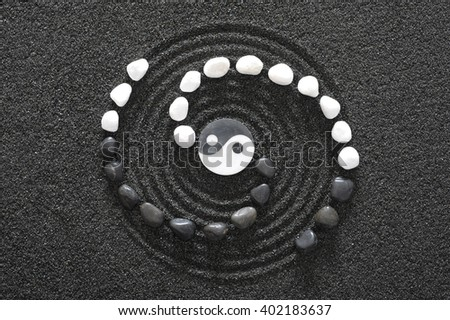 Japanese ZEN garden with yin and yang stone in raked sand - stock photo