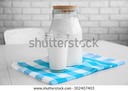 Jar and glass of milk on wooden table, on bricks wall background - stock photo