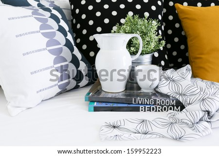 Jar, coffee cup and books with colorful pillows in background - stock photo