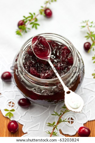 Jar of cranberry jam and some fresh berries on the table - stock photo
