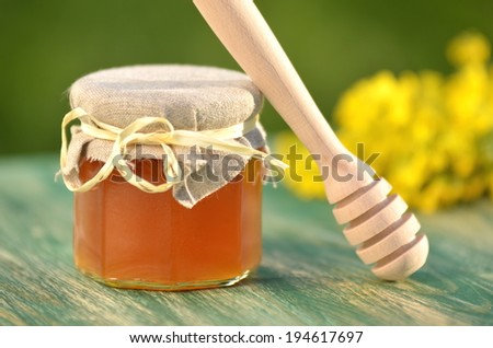 jar of delicious honey with rapeseed flowers and honey dipper - stock photo