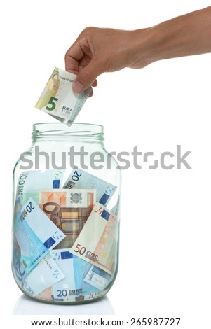 Jar of Euro bills and a hand putting five Euro into it isolated on white. concept.  - stock photo