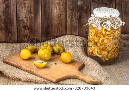 Jar of fruit vodka with quince fruits on a wooden table covered with sackcloth. - stock photo