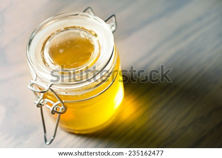 Jar of honey on a wooden table  - stock photo