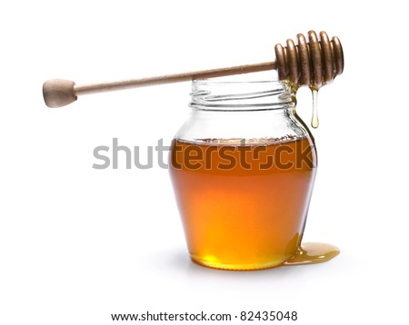 Jar of honey with a wooden drizzler on top. Isolated on white background. - stock photo