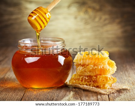 jar of honey with honeycomb on wooden table - stock photo