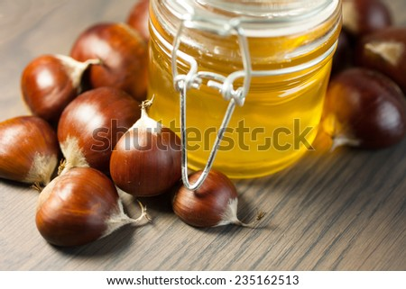 Jar of honey with organic chestnuts on a wooden table   - stock photo