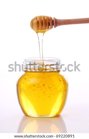 Jar of honey with wooden drizzler on white background - stock photo