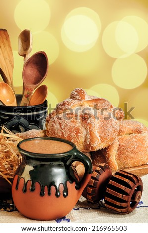 Jar of hot chocolate and sweet bread (pan de muerto) with wooden chocolate grinder and spoons on festive background  - stock photo