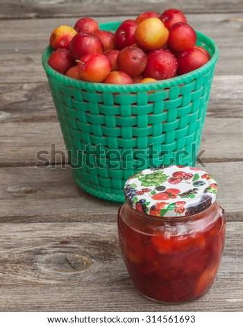 Jar of jam and a basket with red  plums on wooden background - stock photo