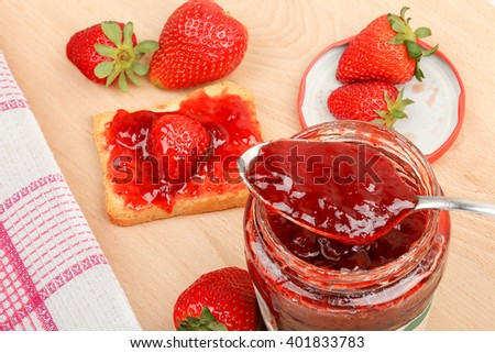 jar of jam with strawberries on wooden table  - stock photo
