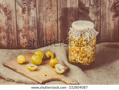 Jar of liquor with quince fruits on a wooden table covered with sackcloth, vintage photo. - stock photo