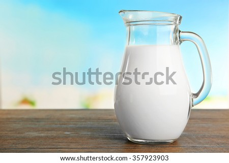 Jar of milk on blurred natural background - stock photo