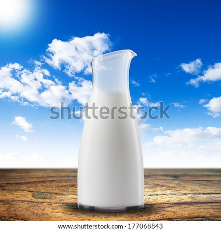 Jar of milk on wood table - stock photo