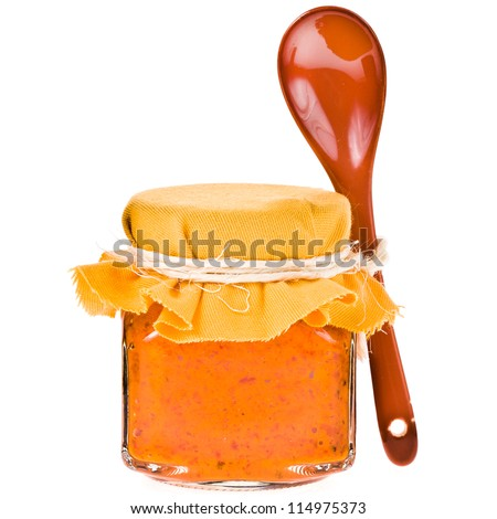 Jar of orange  sauce from the pepper and ceramic spoon isolated on white background - stock photo