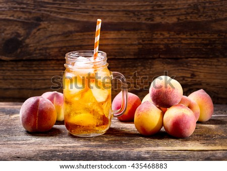 jar of peach iced tea with fresh fruit - stock photo