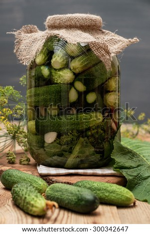 Jar of pickles on wooden table. Homemade cucumber preserved in glass jar. - stock photo