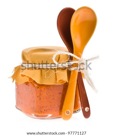 Jar of sauce from the pepper and two tablespoons on white background - stock photo