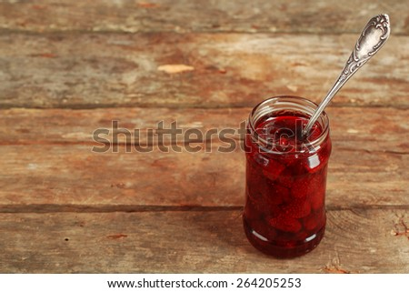 Jar of strawberry jam with spoon on wooden background - stock photo