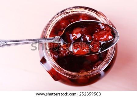 Jar of tasty jam on wooden background - stock photo