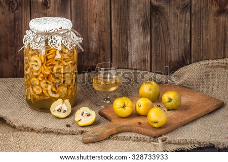 Jar of tincture and glass of tincture with quince fruits on a jute background. - stock photo