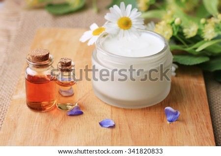 jar of white freshly made skin cream, essential oils bottles, fresh herbs and flowers. Domestic garden ingredients healthy cosmetics - stock photo