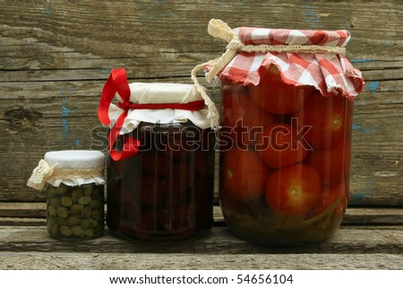 Jar with preserves. Homemade strawberry jam, pickled tomatoes and capers on wooden background. Series - stock photo