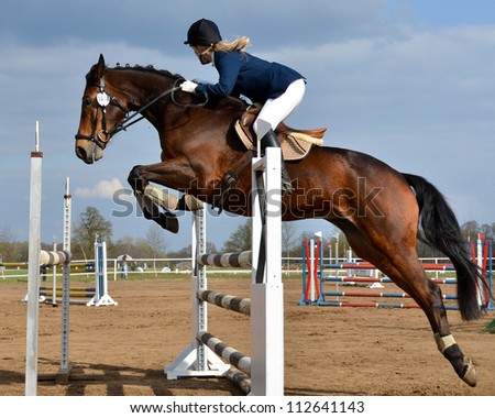 JAROSZOWKA, POLAND - APRIL 16: Unidentified participant jumps with her horse during the international jumping competition on April 16, 2011 in Jaroszowka, Poland. - stock photo