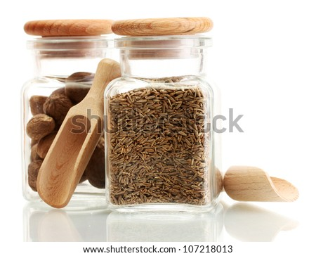 jars and wooden spoons with nutmeg and cumin isolated on white - stock photo