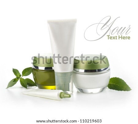 Jars of cream with green leaves isolated on white - stock photo