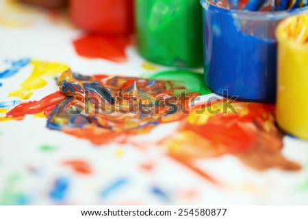 Jars of finger paint on a painting - stock photo