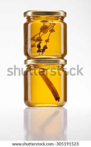 jars of golden honey on a white background with lavender flowers and cinnamon stick inside - stock photo