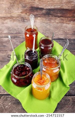 Jars of tasty jam with napkin on wooden background - stock photo