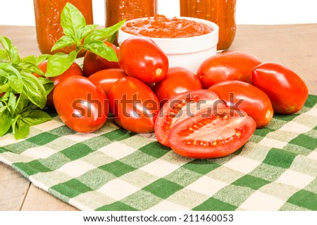 Jars of tomato sauce with fresh basil and red paste tomatoes - stock photo