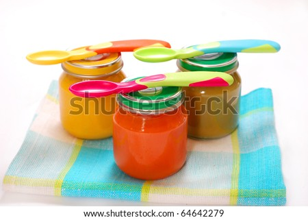 jars of various baby food and spoons isolated on white - stock photo