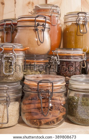Jars with different kind of spices on wood - stock photo