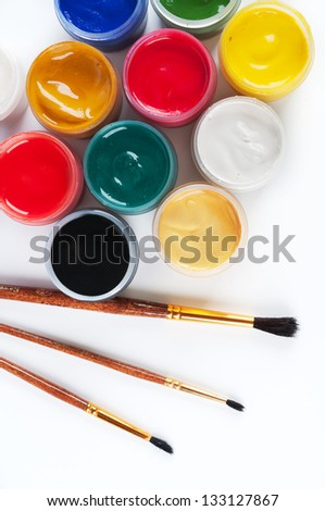 Jars with gouache and paint brushes. On a white background - stock photo