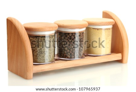 jars with spices on wooden shelf isolated on white - stock photo