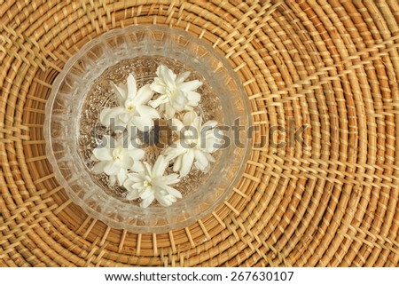 Jasmin flower in glass bowl with wood tray blur background - stock photo
