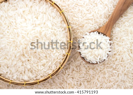 Jasmine rice in a wooden spoon on rice background - stock photo