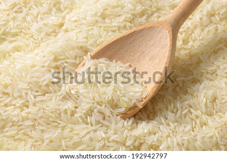 jasmine rice with wooden spoon - stock photo