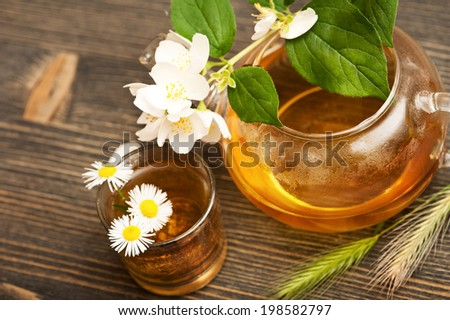 Jasmine tea in a glass tea pot on dark brown wooden background  - stock photo