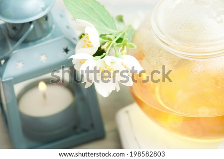Jasmine tea in a glass tea pot on white wooden background with lit lantern. With bokeh - stock photo