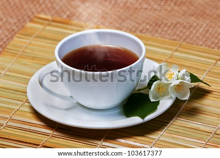 jasmine tea in soft warm evening light with fresh jasmine leaves and flowers - stock photo