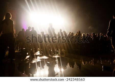 JAZ, MONTENEGRO - JULY 17: People silhouettes infront of the Main Stage at SEA DANCE Music Festival - EXIT ADVENTURE, after a rainy day, on July 17, 2014  at the Jaz beach near Budva, Montenegro. - stock photo