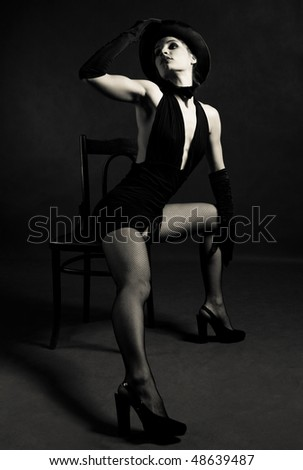 jazz dancer wearing a black cylinder hat, a butterfly bow tie and gloves, dancing with a chair - stock photo