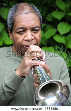 Jazz musician playing a flugelhorn outside. - stock photo