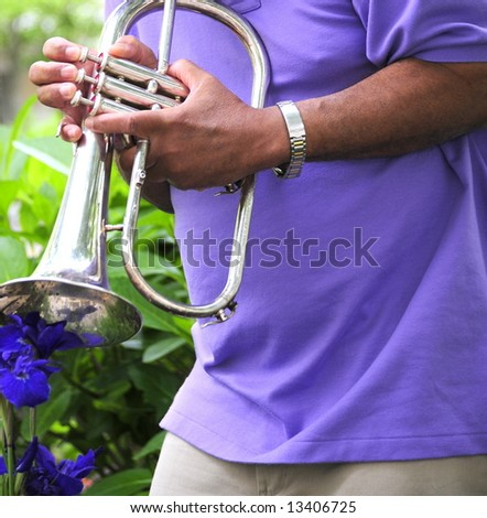 Jazz musician playing his instrument in a flower garden for relaxation. - stock photo