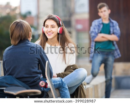 Jealous teen and his happy spanish friends after conflict outdoors  - stock photo