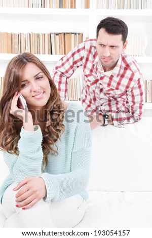 jealous worried man peering over the shoulder of his girlfriend while she is talking on the phone smiling - stock photo